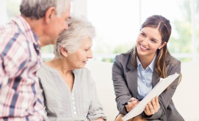 Smiling businesswoman showing documents to senior couple