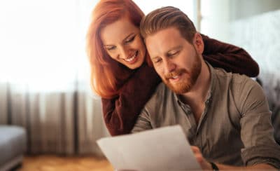 Photo of a happy couple doing finances at home.