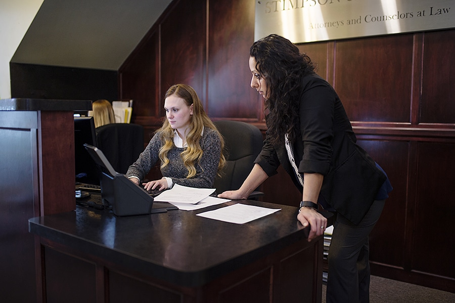 Lawyers reading at front desk in office